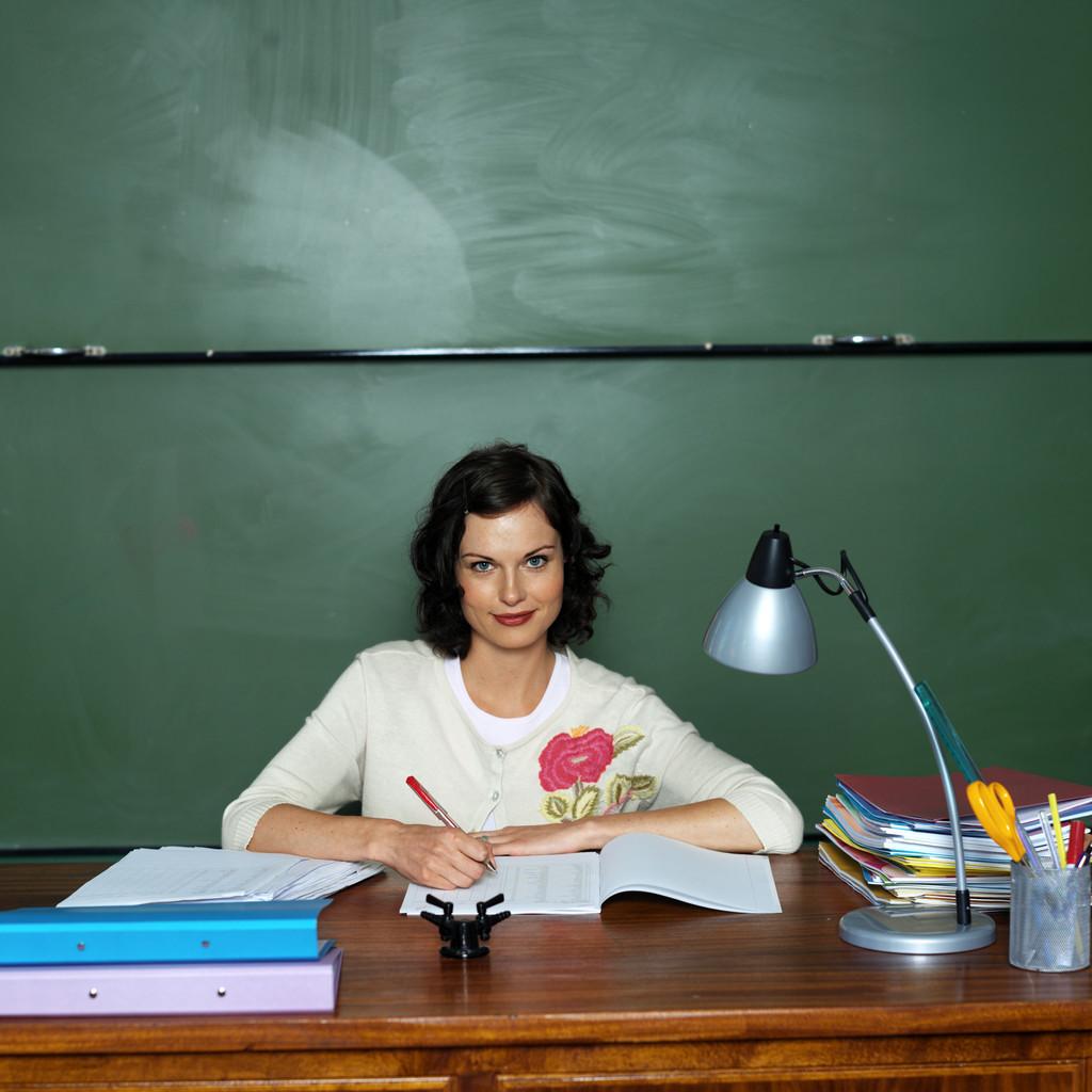 Young School Teacher Working on Her Desk in Class